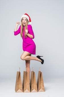 Glimlachend meisje in korte roze jurk en hakken nieuwjaar hoed houden papieren boodschappentassen geïsoleerd op een witte achtergrond