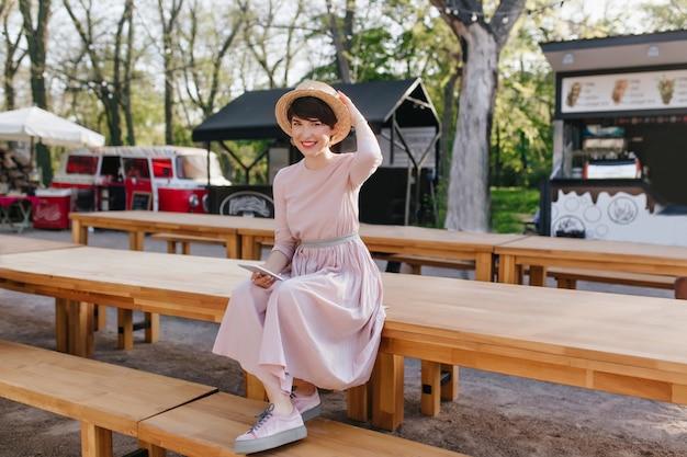 Glimlachend meisje in lange jurk en trendy schoenen, zittend op houten tafel met mobiele telefoon in de hand