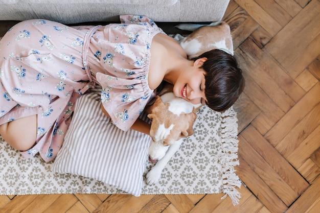 Glimlachend meisje in mooie lange jurk ligt op beagle hond met gesloten ogen. portret van bovenaf van aantrekkelijke lachende dame koelen op tapijt met haar huisdier