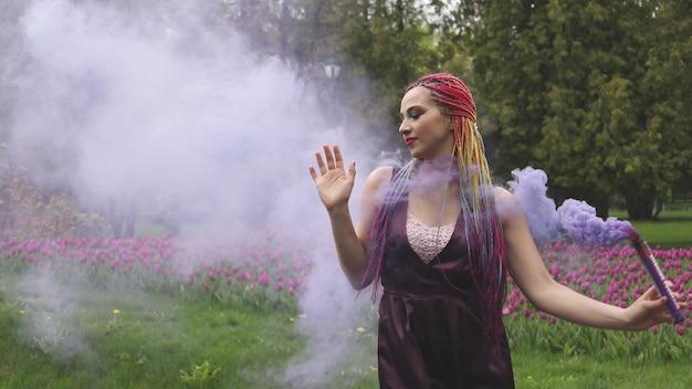 Glimlachend meisje in paarse satijnen jurk met lange veelkleurige vlechten en opvallende glitter make-up. rook van paarse kleur bedekt het meisje in het lentepark