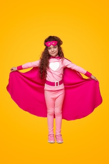 Glimlachend meisje in roze superheld outfit