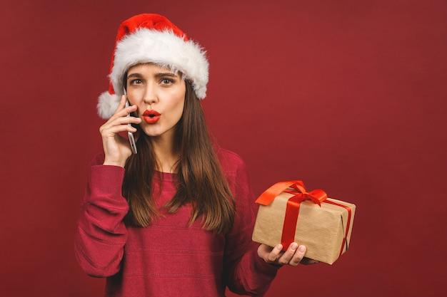 Glimlachend meisje in santa kleren met kerstcadeaus bellen op telefoon.