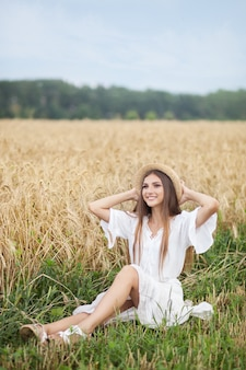 Glimlachend meisje in strohoed en in witte kleding die van aard van tarwegebied genieten. zomervakantie
