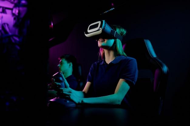 Glimlachend meisje in virtual reality-bril, zittend in de leunstoel van gamers en het gebruik van joystickgreep tijdens het spelen van videogame in computerclub