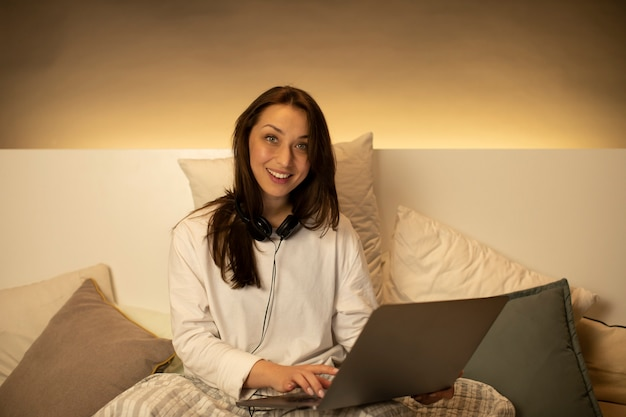 Glimlachend meisje in vrijetijdskleding en hoofdtelefoons die bij laptop zitting in bed werken