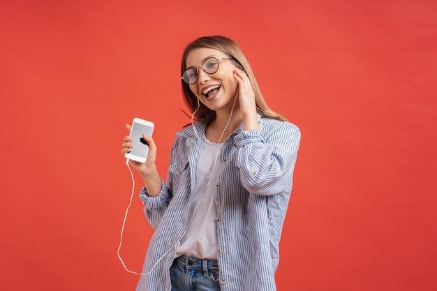 Glimlachend meisje in vrijetijdskleding en oortelefoons dansende bewegende handen.
