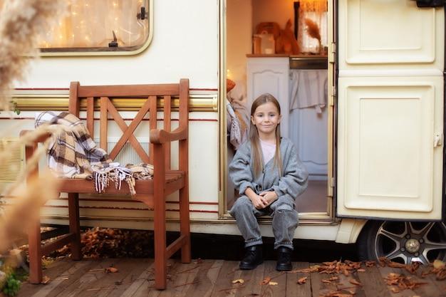 Glimlachend meisje in vrijetijdskleding zit in de buurt van de deur van de trailer op het rv-huis van de veranda in de tuin