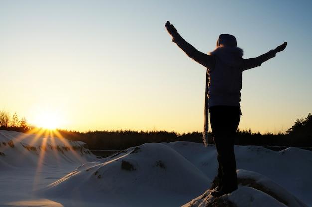 Glimlachend meisje in wit winterjasje, blauwe gebreide sjaal en zwarte broek, gehurkt onder de besneeuwde gracht in het bos