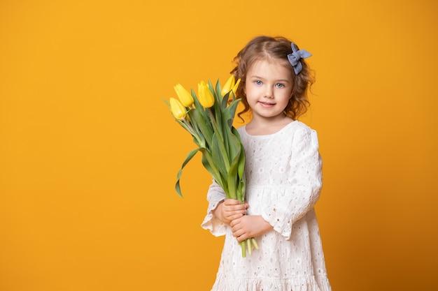 Glimlachend meisje in witte kleding op geel
