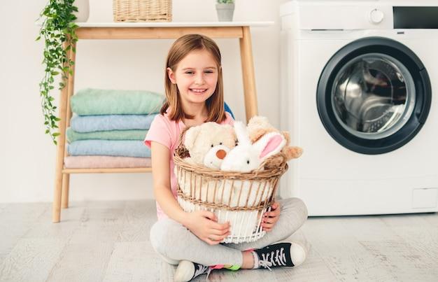 Glimlachend meisje knuffels houden in de wasmand zittend op de vloer in de badkamer