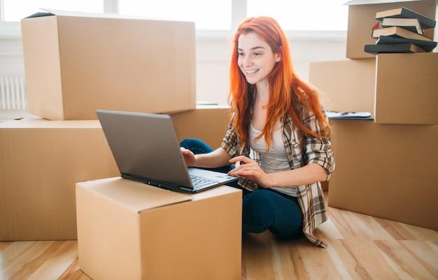 Glimlachend meisje met behulp van laptop onder kartonnen dozen, verhuizen naar een nieuw huis, inwijdingsfeest