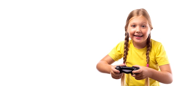 Glimlachend meisje met blond haar speelt een computerspel op een spelcomputer. zwarte joystick in de handen van een vrolijk kaukasisch meisje op een witte achtergrond