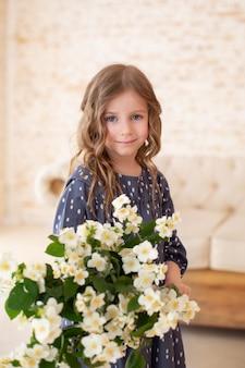 Glimlachend meisje met boeket jasmijnbloemen kindmeisje met boeket bloemen voor mama