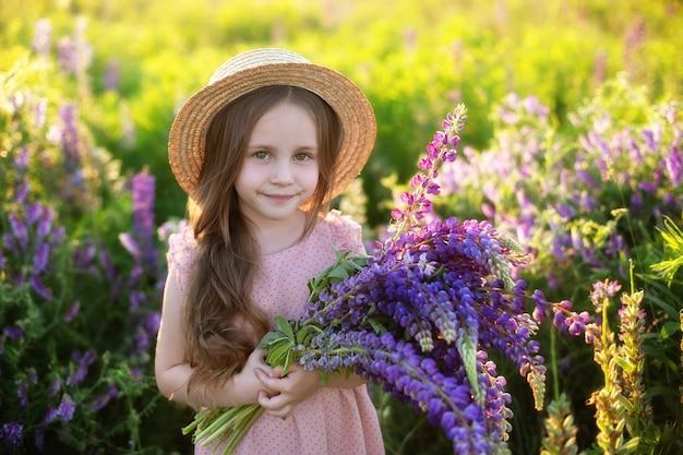 Glimlachend meisje met boeket lupines in de zomerweide een kindmeisje in een veld met lupinespine
