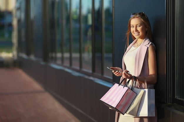 Glimlachend meisje met boodschappentassen met telefoon in de hand. winkelier. verkoop.