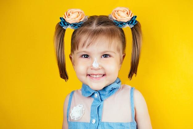 Glimlachend meisje met crème op gezicht op homogene achtergrond. bescherming tegen de zon, spf - concept