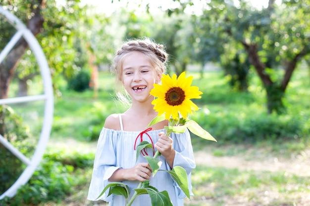 Glimlachend meisje met een staartje op haar hoofd houdt zonnebloem vast in de tuin kind met zonnebloem