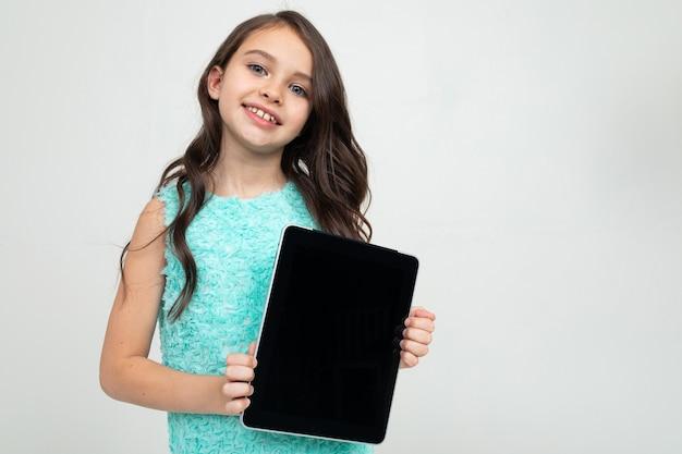 Glimlachend meisje met een tablet met een sjabloon voor het invoegen van een webpagina of advertentie op een witte achtergrond.