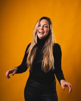 Glimlachend meisje met geboren blonde haarwortels bekijkend de camera die zwarte overhemd en broek draagt