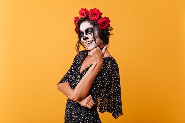 Glimlachend meisje met gezichtskunst voor carnaval verschijnt duim, poseren in zwarte outfit op geïsoleerde achtergrond.