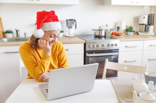 Glimlachend meisje met kerstmuts met videobellen familie door webcam. vrouw met laptop zittend op de keuken thuis met behulp van virtuele vergaderchat op vakantie. fijne kerst en nieuwjaar nieuwe normaal.