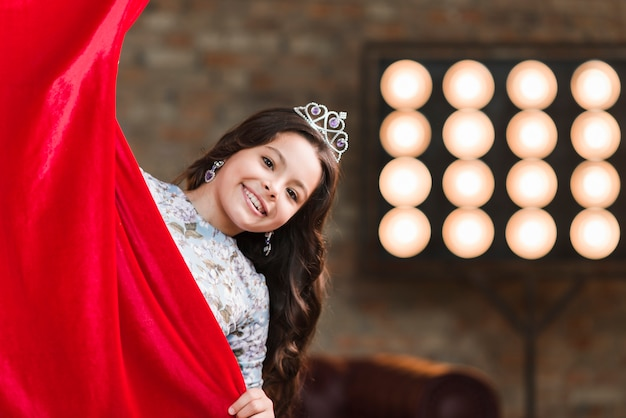 Glimlachend meisje met kroon op haar hoofd die van rood gordijn gluren