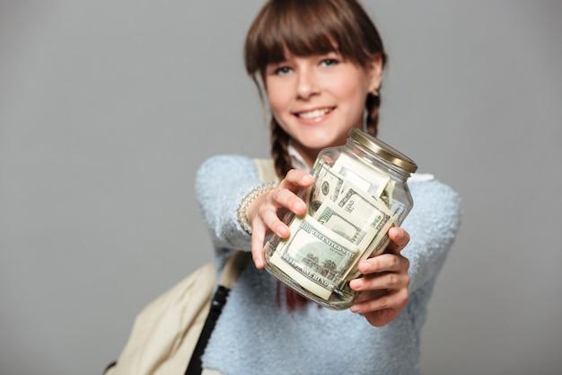 Glimlachend meisje met kruikhoogtepunt van geld
