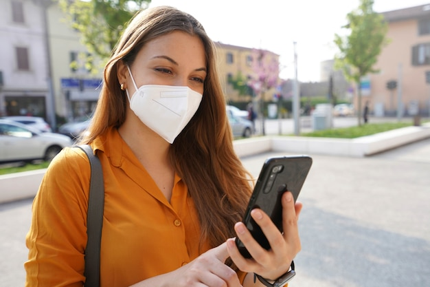 Glimlachend meisje met masker dat haar telefoon op straat controleert