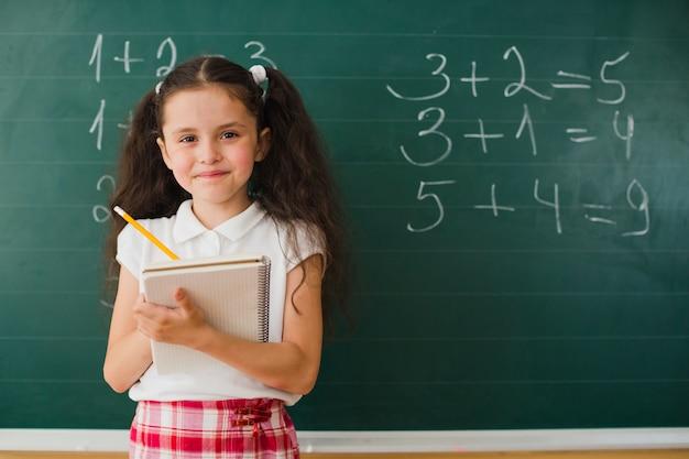 Glimlachend meisje met notitieblok in de klas