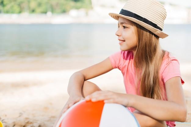 Glimlachend meisje met opblaasbare bal bij strand