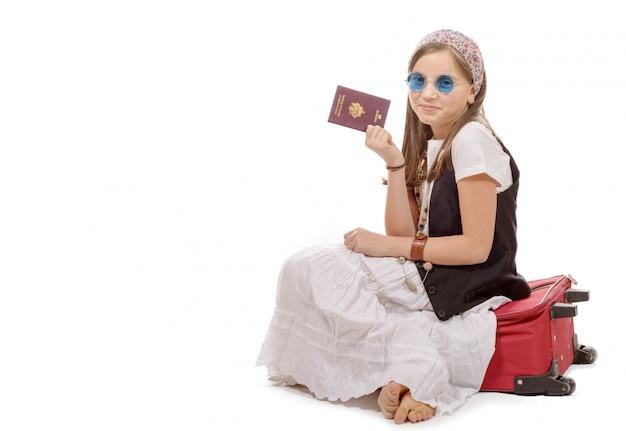 Glimlachend meisje met reiszak, paspoort dat over wit wordt geïsoleerd