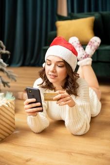 Glimlachend meisje met smartphone en creditcard dichtbij kerstboom. online winkelen in het nieuwe jaar. ze koopt cadeautjes