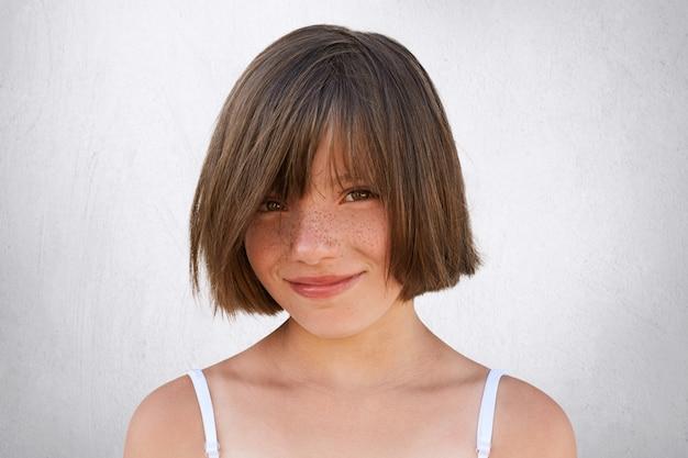 Glimlachend meisje met stijlvol kapsel, donkere ogen en sproeten gezicht poseren tegen wit