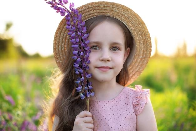 Glimlachend meisje met strohoed houdt lupinebloem vast meisje in het veld met lupines zomervakantie