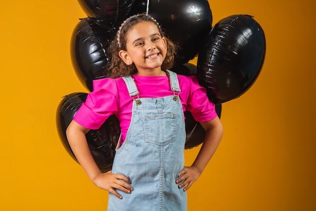 Glimlachend meisje met zwarte ballonnen op zwarte vrijdag. lage prijs festival