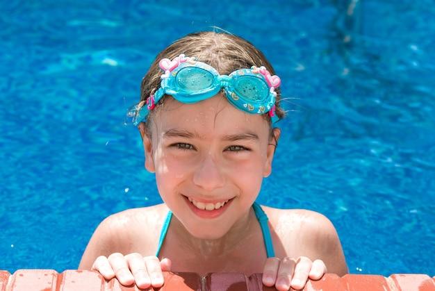 Glimlachend meisje met zwembril in zwembad