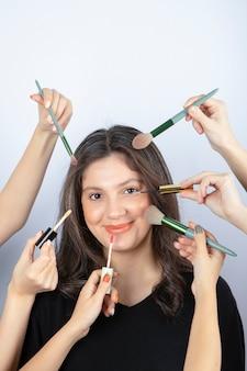 Glimlachend meisje omringd door handen van make-upartiesten met borstels, lippenstift en mascara in de buurt van haar gezicht.