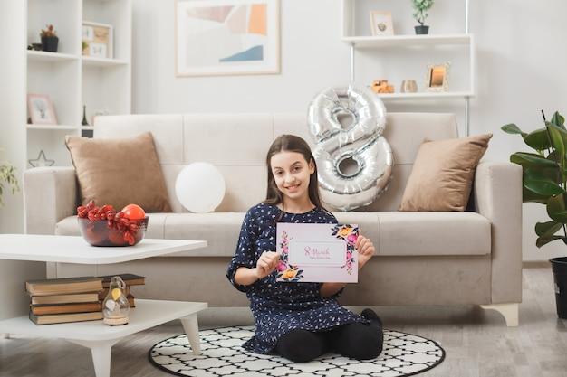 Glimlachend meisje op een gelukkige vrouwendag zittend op de vloer met een wenskaart in de woonkamer