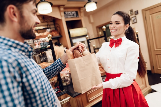 Glimlachend meisje pakket met brood geven aan de mens