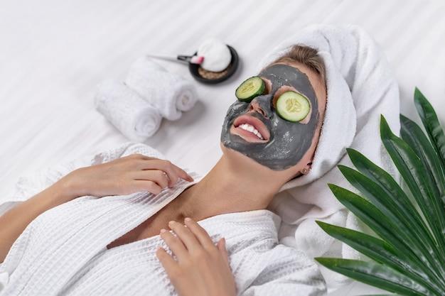 Glimlachend meisje poseren met een kleimasker op haar gezicht