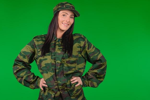 Glimlachend meisje, professionele soldaat poseren op groene achtergrond met lege ruimte voor uw advertentie