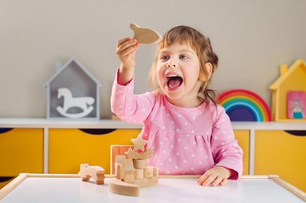 Glimlachend meisje speelt met houten raket op tafel in de kinderkamer