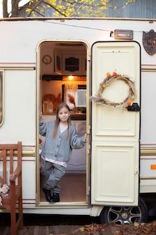 Glimlachend meisje staande in de buurt van caravan deur veranda rv huis in de tuin