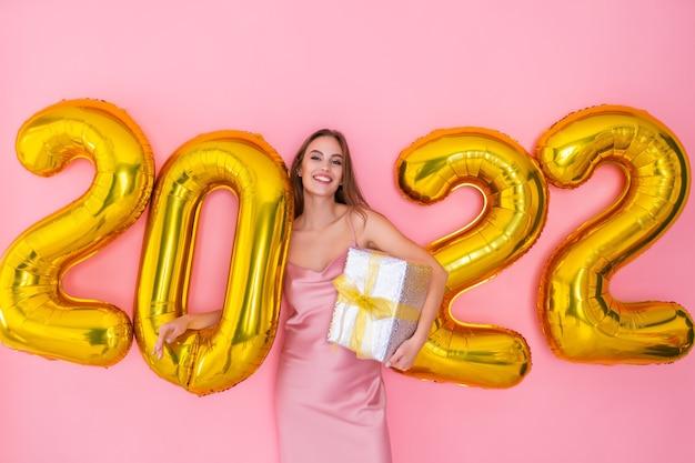 Glimlachend meisje staat in de buurt van luchtballonnen houdt geschenkdoos op roze achtergrond nieuwjaarsviering