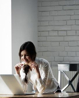 Glimlachend meisje werken met laptop in de ochtend, luisteren naar muziek met een koptelefoon, studeren, werken met onderwijsproject. jonge zakenvrouw, vrouwelijke freelancer. een casual wit overhemd dragen.