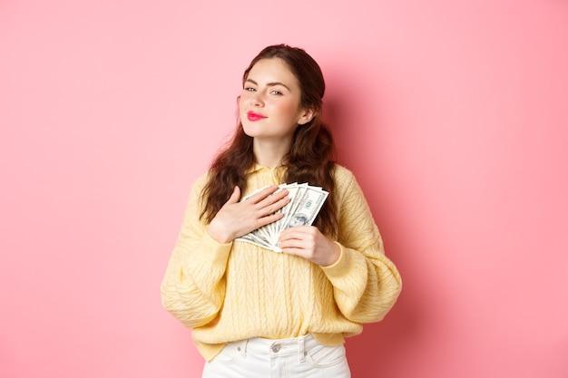 Glimlachend meisje ziet er tevreden en dankbaar uit, knuffelt dollarbiljetten, houdt geld vast en maakt een zelfvoldaan gezicht, staande tegen een roze achtergrond