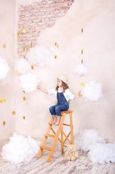 Glimlachend meisje, zittend op de trap in de lucht met wolken en met de sterren. meisje vliegt in de lucht.