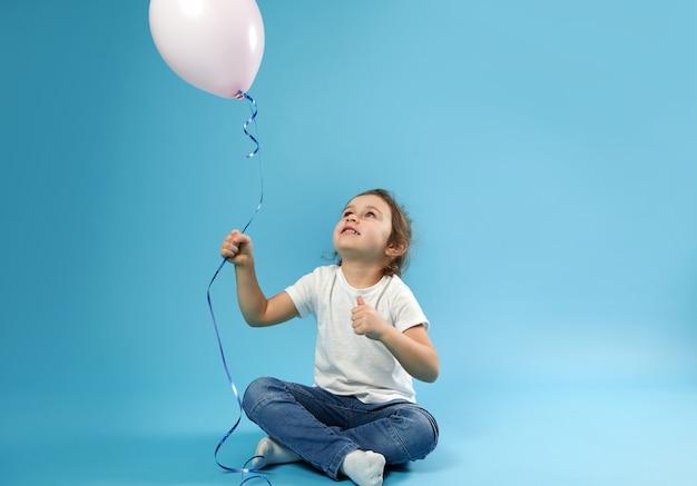 Glimlachend meisje, zittend op een blauwe ondergrond met zachte schaduw en ballonnen in de hand te houden