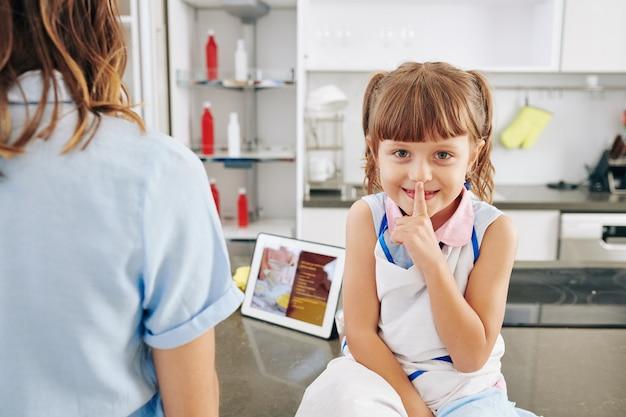 Glimlachend meisje zittend op het aanrecht en stilte gebaar maken wanneer haar moeder diner kookt