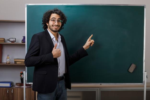 Glimlachend met duim omhoog jonge mannelijke leraar die een bril draagt, wijst naar het bord in de klas
